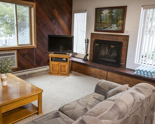 A well furnished living room with a fireplace television and an outdoor view.