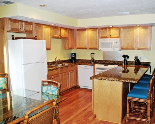 A well equipped kitchen with a breakfast bar and glass top dining table.