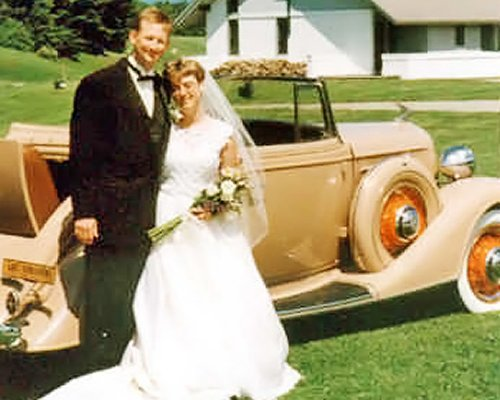 A newly married couple standing alongside a vintage car.