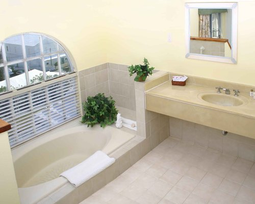 A bathroom with bathtub shower and vanity.