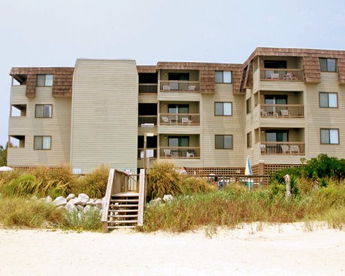 A beach view of multi story units alongside shrubs.