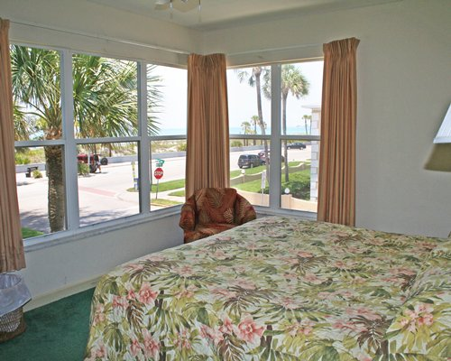 A well furnished bedroom with queen bed and outdoor view.