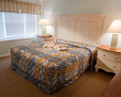 A well furnished bedroom with a queen size bed and an outdoor view.