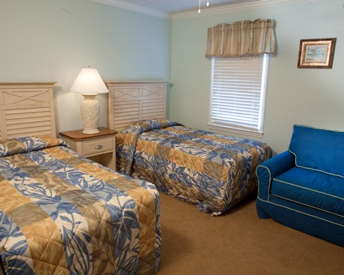 Furnished bedroom with two twin beds a chair and outside view.