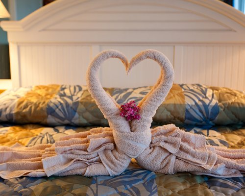 Two towels crafted as a heart placed on a queen size bed.