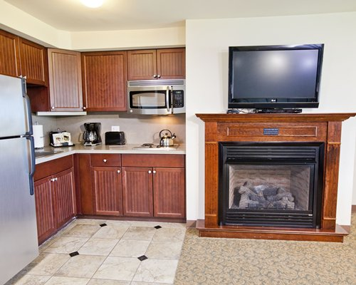 A well equipped kitchen alongside a fireplace and a television.