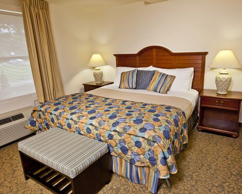 A well furnished bedroom with a king size bed and an outdoor view.
