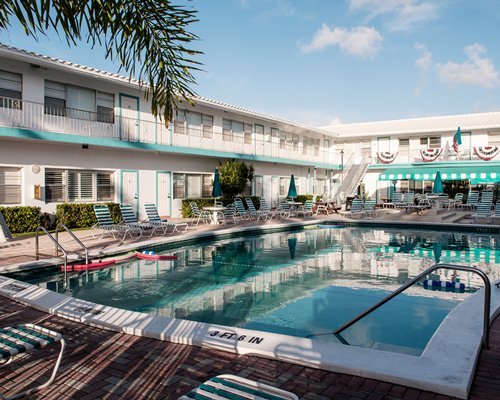 Outdoor swimming pool with chaise lounge chairs and view of multiple unit balconies.