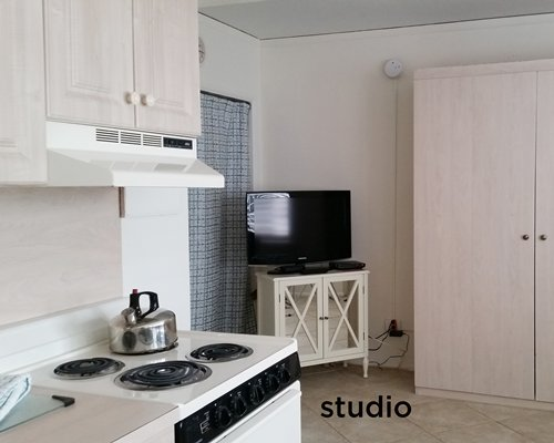 An open plan studio with kitchen and television.