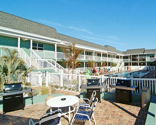 An outdoor dining area with a barbecue grill alongside a multi story unit and swimming pool.