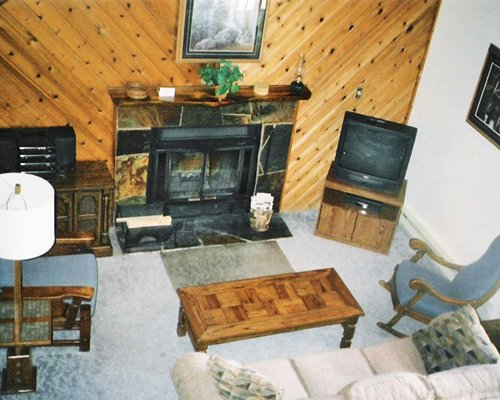 A well furnished living room with a fireplace and a television.