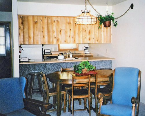 A well furnished dining and kitchen with a breakfast bar.