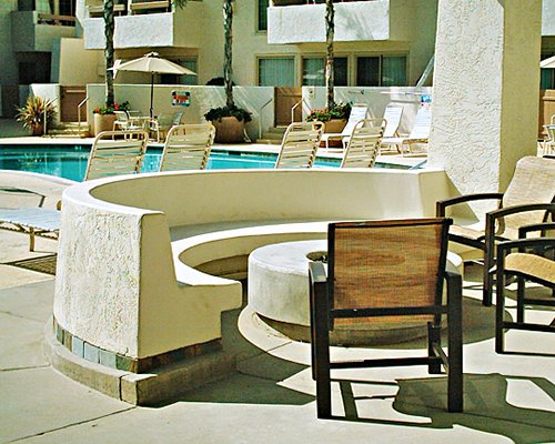 An outdoor dining area alongside a swimming pool and chaise lounge chairs.