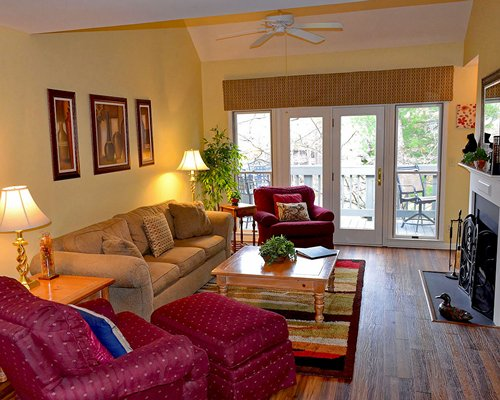 A well furnished living room with fireplace balcony and outdoor view.