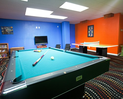 A recreational room with pool table table tennis and a television.