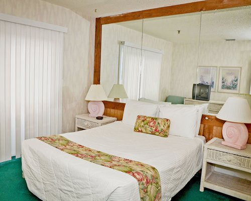 A well furnished bedroom with queen bed and television.