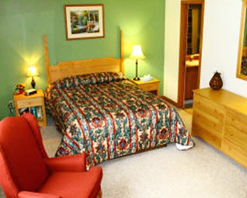 A well furnished bed room with queen bed and patio furniture.