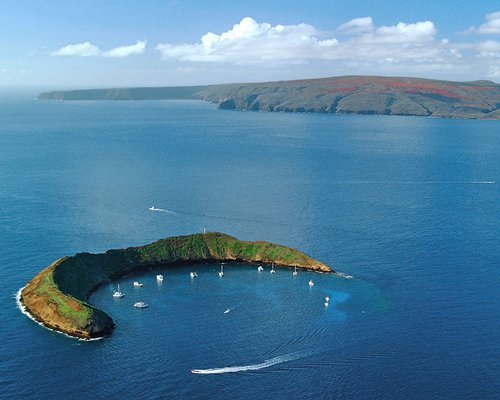 An aerial view of Molokini crescent shaped crater with yachts.
