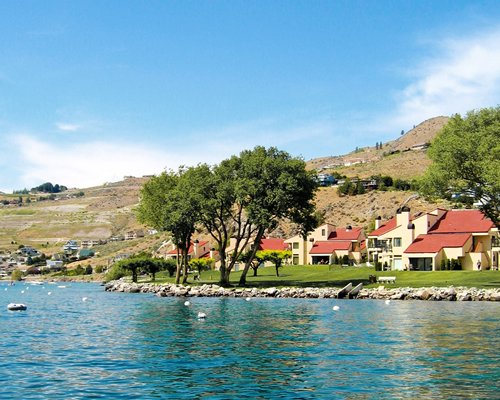 A lake view of the Lake Chelan Shores resort located at the foot of a hill.