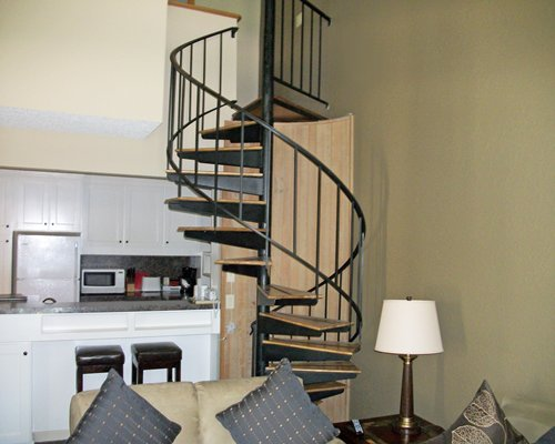 An open plan living room with kitchen alongside spiral stairs.