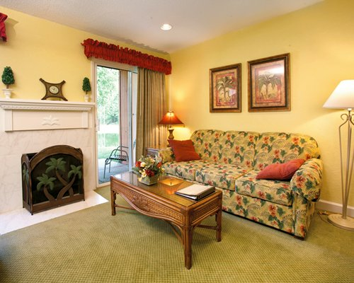 A well furnished living room with a double pull out sofa fireplace and a patio.