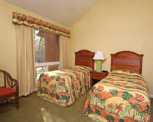 Furnished bedroom with two twin beds and outside view.