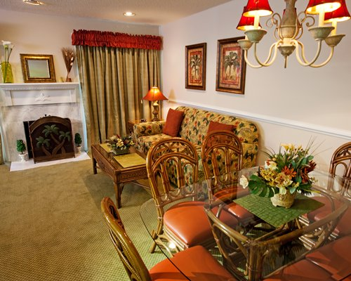 A well furnished living room with dining area and fireplace.