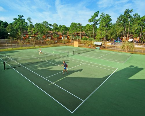 An outdoor tennis court surrounded by wooded area.