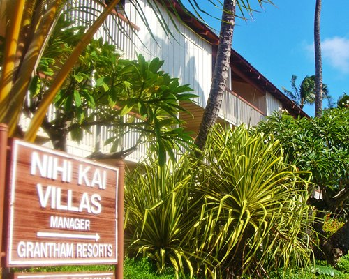Signboard of Nihi Kai Villas with landscaped exterior view of villa balconies.