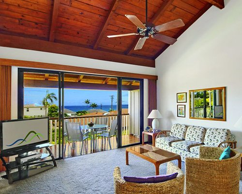 A well furnished living room with television and balcony with patio table and ocean view.
