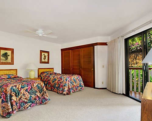 A furnished bedroom with two twin beds and a patio.