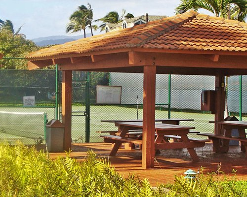 A wooden sitting area alongside the tennis courts.