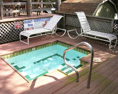 An outdoor kiddie pool with chaise lounge chairs.