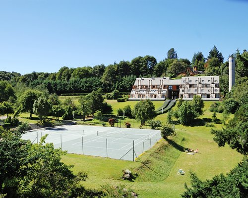 An outdoor tennis court alongside multi story units surrounded by wooded area.
