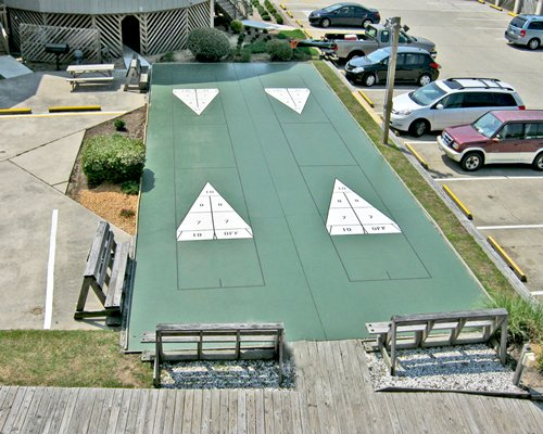 Outdoor shuffleboard courts alongside a car parking area.