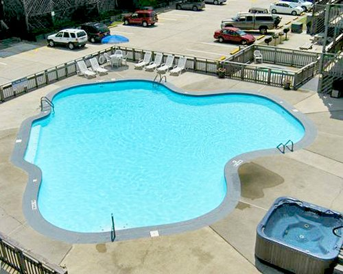 An outdoor swimming pool with hot tub alongside parking area.
