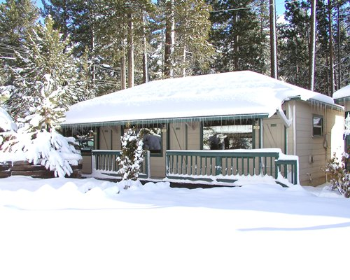 An exterior view of Tahoe Sands Resort covered with snow.