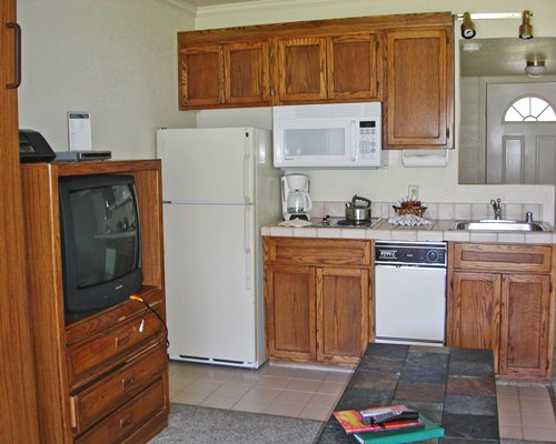 A well equipped kitchen alongside a television.