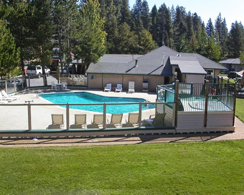 Scenic outdoor swimming pool and hot tub with chaise lounge chairs surrounded by wooded area.