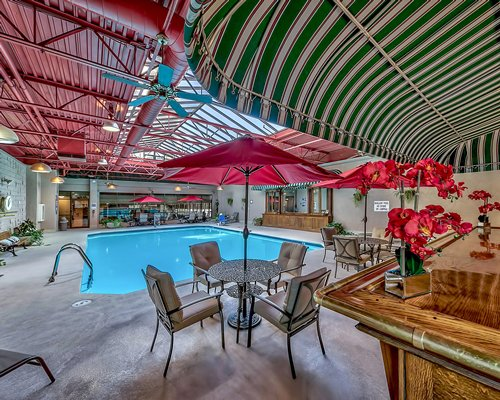 Indoor swimming pool with patio chairs and umbrella.
