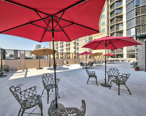 A view of sunshades with patio furniture alongside a multi story studios.