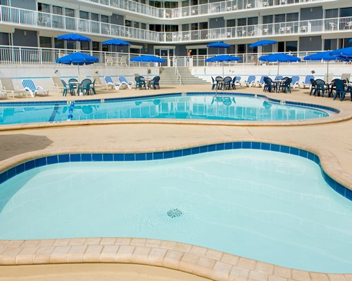 Outdoor swimming pool with hot tub alongside multi story units.