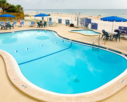 Outdoor swimming pool with sunshades and chaise lounge chairs overlooking the beach.
