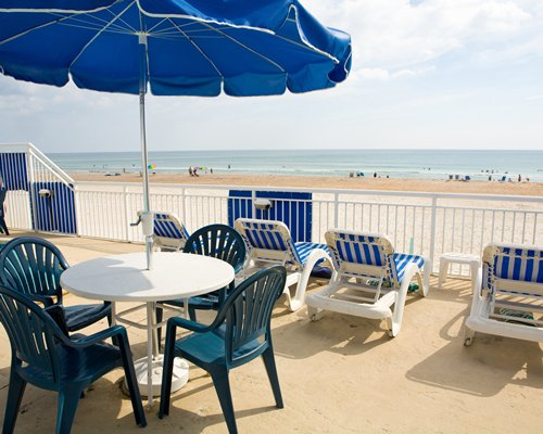 Beach view with lounge chairs and umbrella.