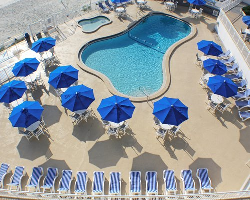 An aerial view of outdoor swimming pool with chaise lounge chairs and sunshades.