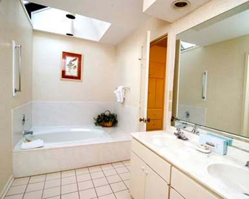 A bathroom with double sink vanity and a shower.