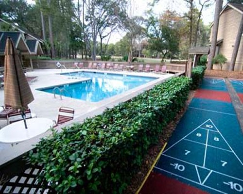 An outdoor shuffle boards alongside swimming pool.