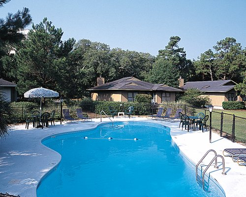 An outdoor swimming pool alongside resort units surrounded by wooded area.
