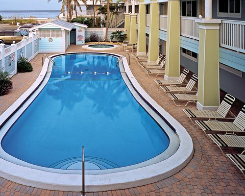 An outdoor swimming pool with chaise lounge chairs alongside resort.