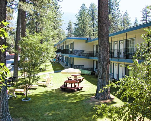 An exterior view of multi story suites from the woods.